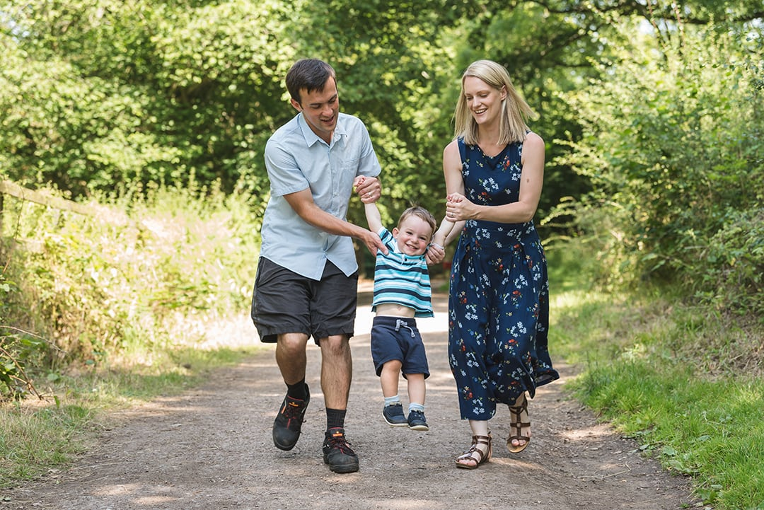 Mother and Father skip with son in natural Essex family session