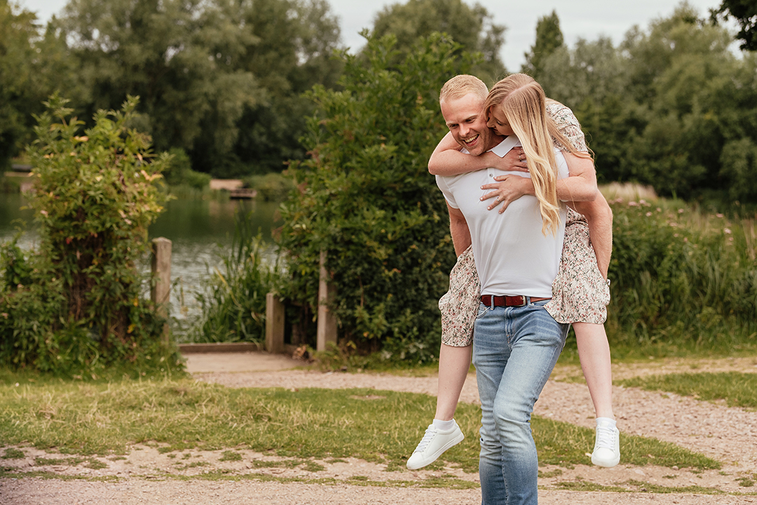 Groom gives his bride a piggy back during Pre Wedding Photos at Stanborough Lake