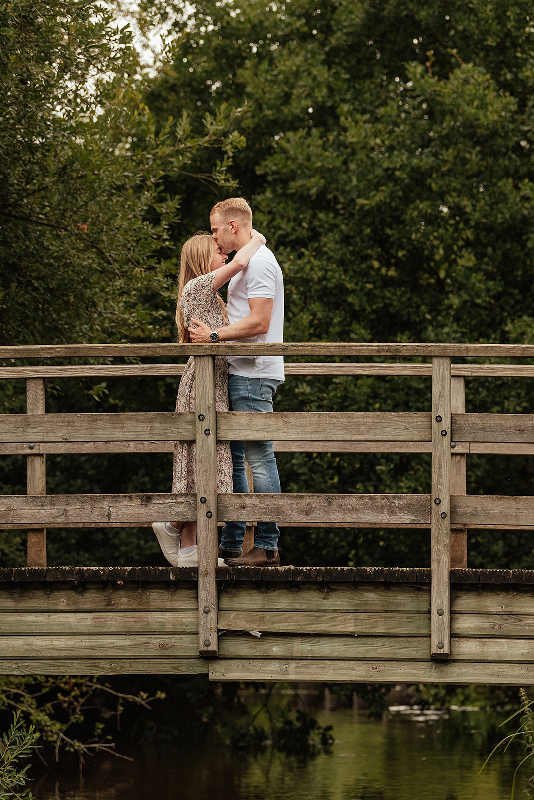 Bride pulls groom in close on bridge in Natural Pre Wedding Photoshoot at Stanborough Lake