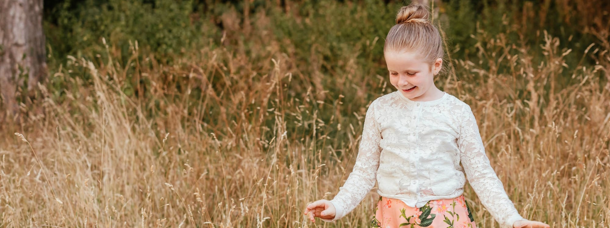 Girl plays in tall grass looking down and smiling, really cute family photo