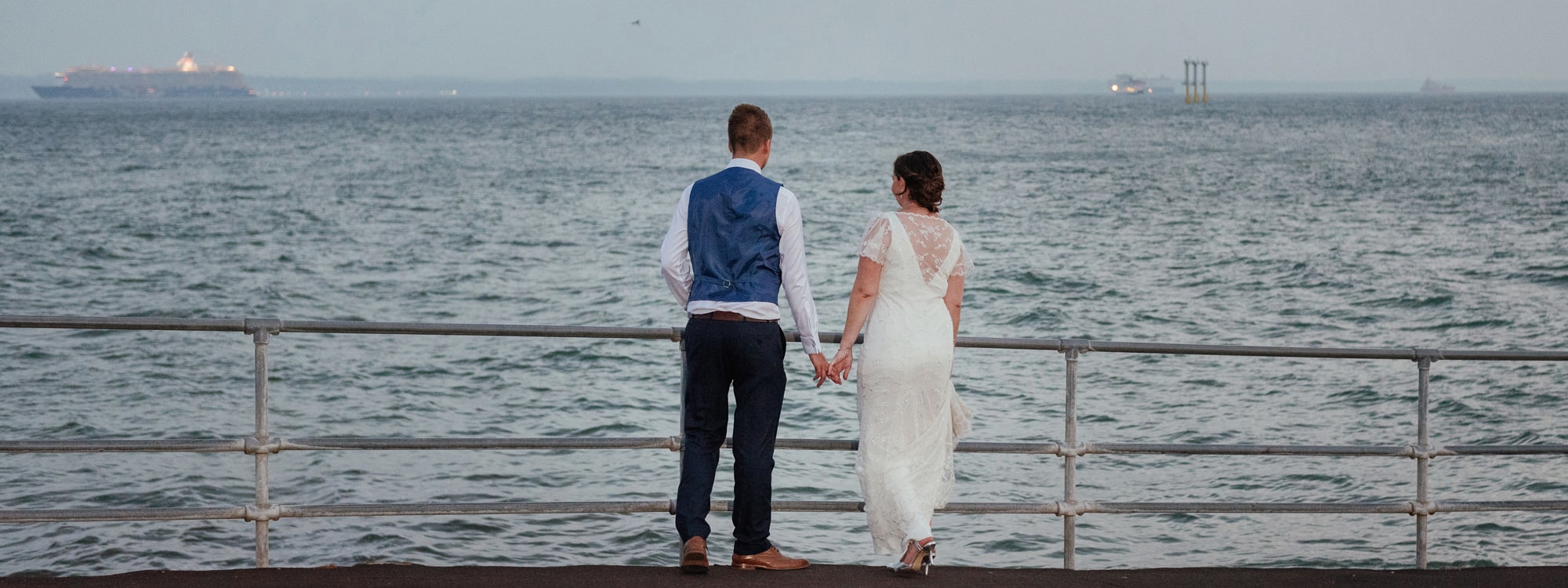 Essex Wedding by the Sea Couple stand and hold hands looking out at the sea