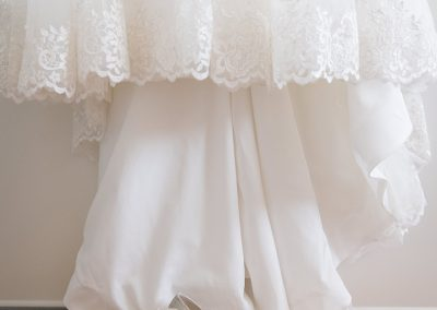 Bridal gown hangs above the bridal shoes