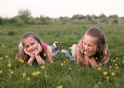 Girls laying in buttercups in Harlow Essex photo session