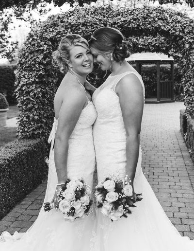 Black and white natural candid moment of two brides during couples portraits