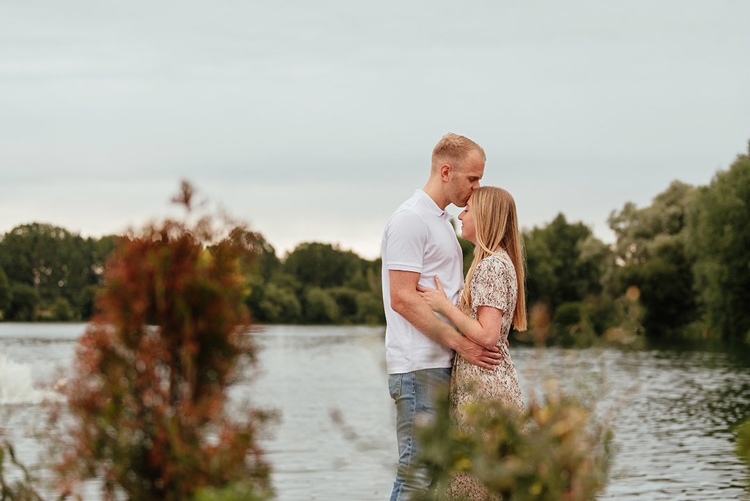 Couple behind the plants in front of the lake enjoying a private moment where he kisses her on the head at Stanborough Lake Couples Pre Wedding Photos