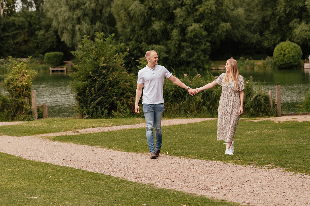 Couple walk together arms outstretched Stanborough Lake Engagement Photos
