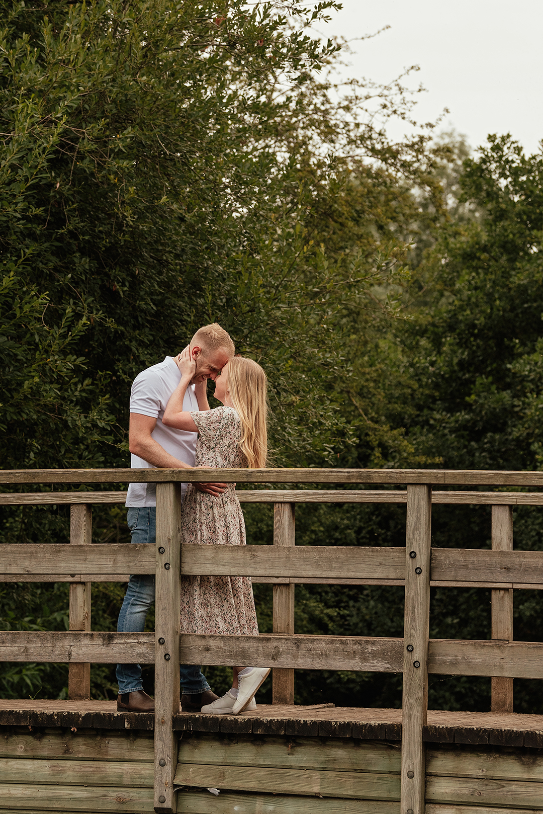 Full length image of Bride pulls groom in for intimate moment on bridge in Natural Pre Wedding Photoshoot at Stanborough Lake