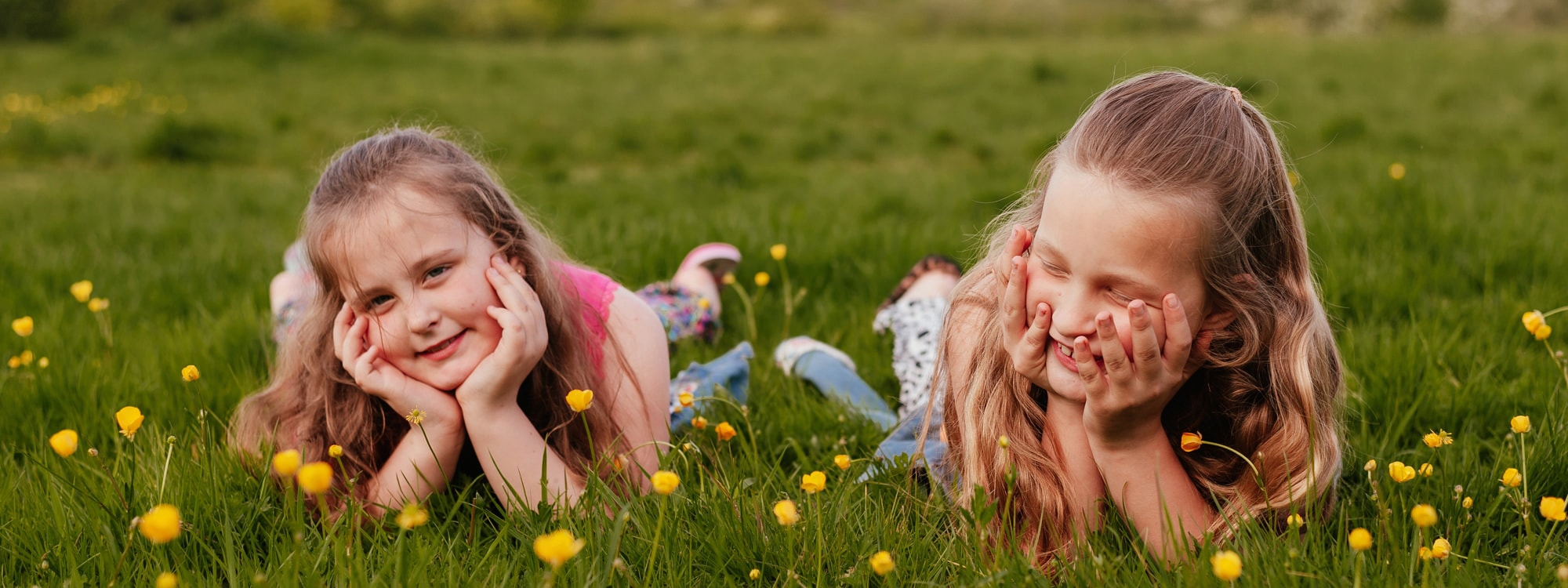 Twin girls lay together in buttercups in cute family photography Essex