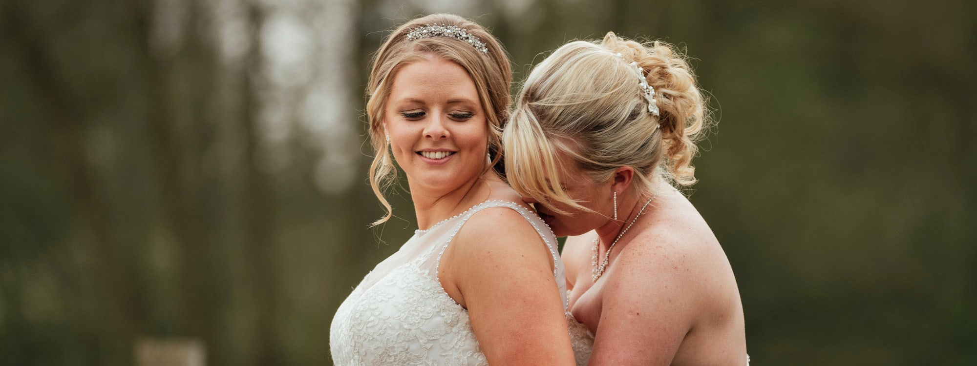 Two brides sit together, one kisses the other on her shoulder at Tewin Bury Farm Hotel, Hertfordshire