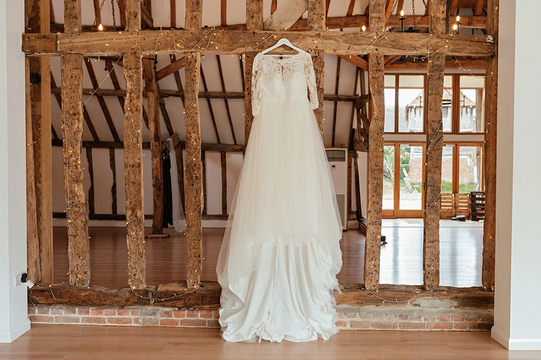 Wed2B Dress Hanging on Wooden Beam in Mil Pond Barn Colville Hall