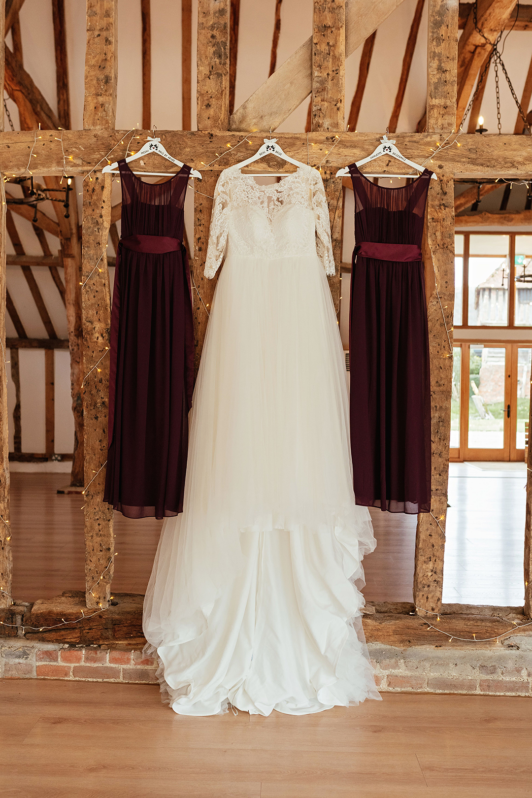 Wed2B Wedding Dress and Purple Bridesmaid Dresses Hanging on Wooden Beam in Mil Pond Barn Colville Hall