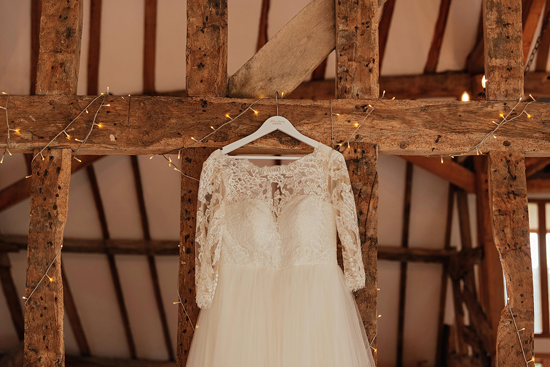 Close up of Top Half of Wed2B Dress Hanging on Wooden Beam in Mil Pond Barn Colville Hall