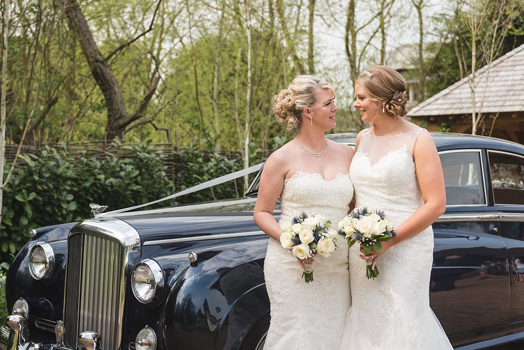 Two brides share a moment together while stood in front of wedding car
