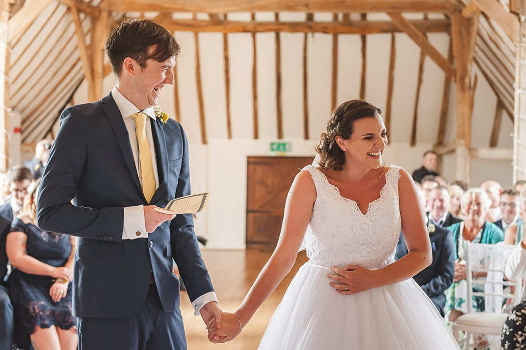 Intimate wedding ideas Couple laughing during wedding vows