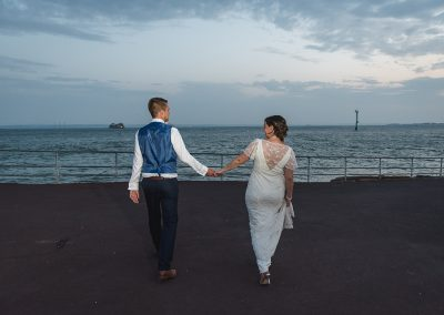Cute natural image of bride and groom walking away from camera towards the sea